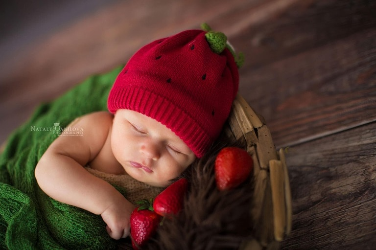 newborn baby wearing strawberry hat