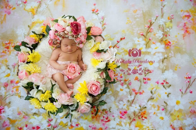 newborn girl in a pink yellow flower bonnet