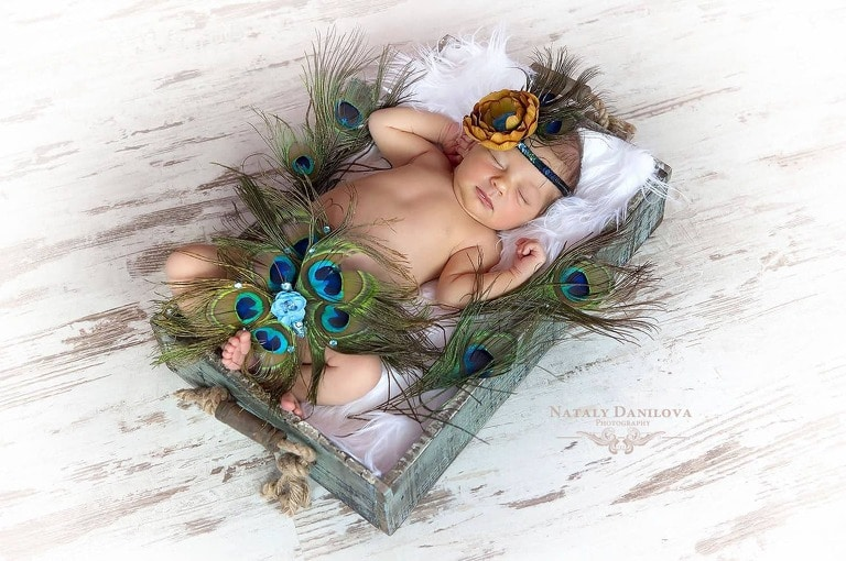 newborn baby girl with a peacock accessories